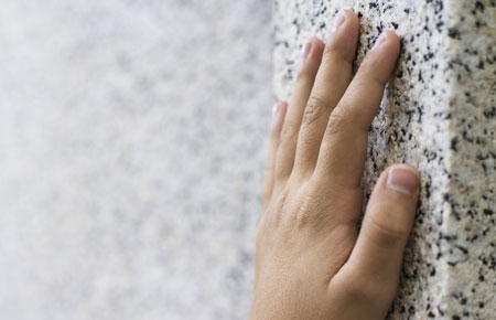 hand on granite wall