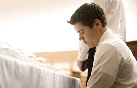 Priest kneeling in prayer at the sacrament table