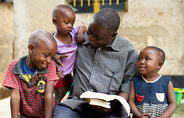 father reading scriptures to his children