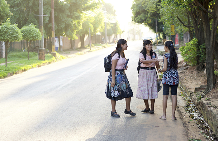 sister missionaries greeting woman
