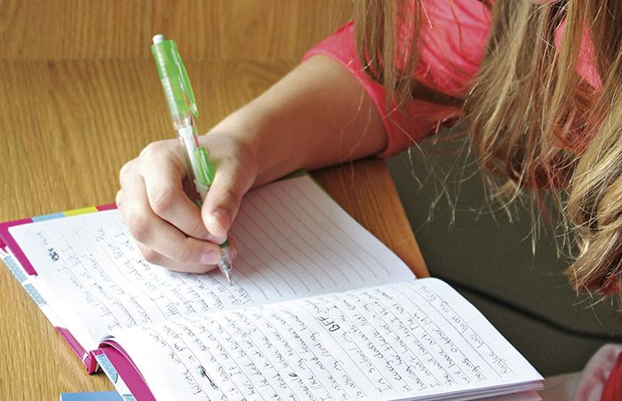 youth writing in a journal