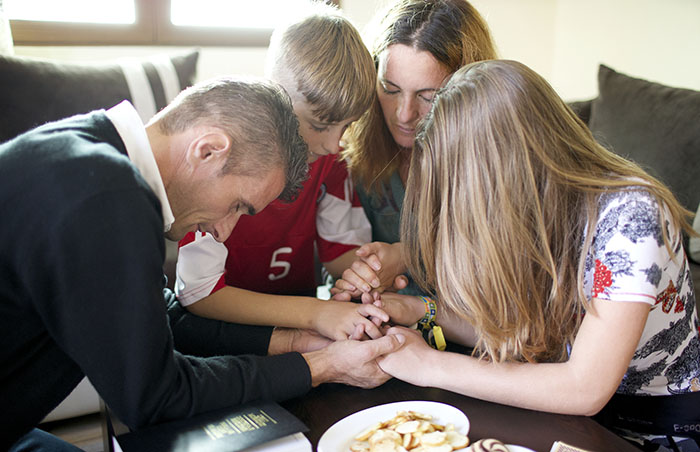 ilir and family kneeling in prayer