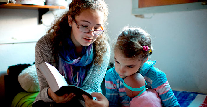 young woman reading scriptures with younger sister