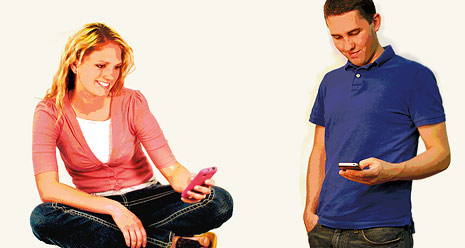 young man and woman looking at cell phones