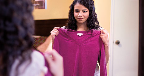 young woman looking at shirt in mirror