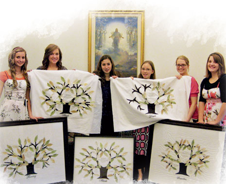 young women holding embroidered family trees
