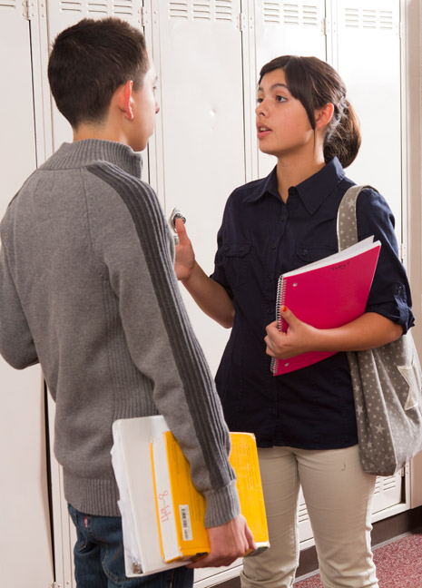 young man and young woman by school lockers