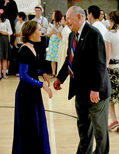 young woman and old man dancing