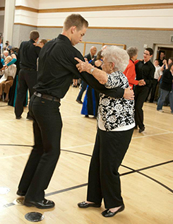 young man and old woman dancing