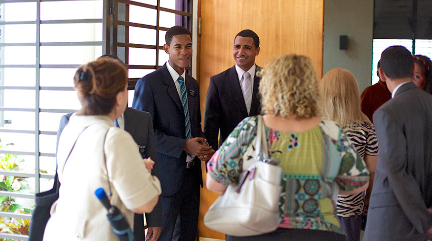 Missionaries greeting a group of people