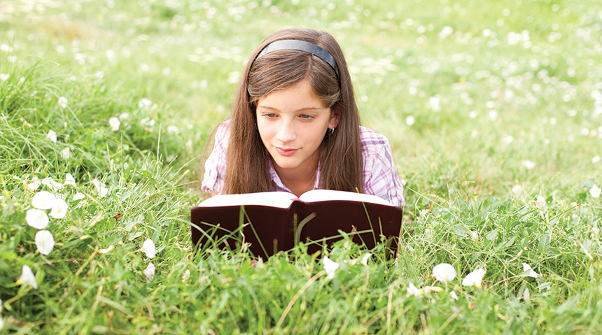 Young girl reading the scriptures in a field