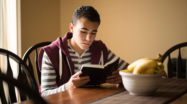 Young man reading Book of Mormon
