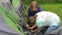 Two young women setting up a tent